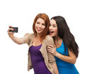 Two smiling teenagers with smartphone technology friendship and people concept taking picture camera Stock Photos
