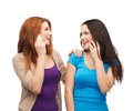Two smiling teenagers with smartphones technology friendship and leirure concept talking Royalty Free Stock Photo