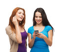 Two smiling teenagers with smartphones technology friendship and leirure concept texting and calling Stock Photo