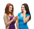 Two smiling teenagers with smartphones technology friendship and leirure concept texting and calling Royalty Free Stock Image