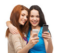 Two smiling teenagers with smartphones technology friendship and people concept Stock Images