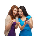 Two smiling teenagers with smartphones technology friendship and people concept pointing finger at smartphone screen Royalty Free Stock Image