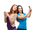 Two smiling teenagers with smartphones technology friendship and people concept taking picture smartphone camera Stock Image