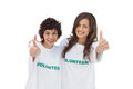 Two smiling volunteers giving thumbs up on white background Stock Image