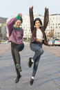 Two smiling woman jumping in the street. Royalty Free Stock Photo