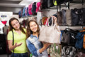 Two smiling women choosing bag in shop Royalty Free Stock Photo