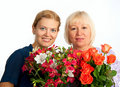 Two smiling women with flowers on white background Royalty Free Stock Photo