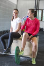 Two smiling women rests at fitness gym center fit attractive and happy taking a break and drink water after workout Royalty Free Stock Photo