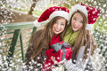 Two smiling women santa hats holding a wrapped gif attractive festive mixed race wearing christmas bow gift outside with snow Stock Photos