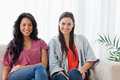 Two smiling women sit on the couch together while looking at the Stock Photo
