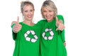 Two smiling women wearing green recycling tshirts giving thumbs up