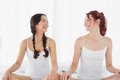 Two smiling women in white tank tops sitting on bed Royalty Free Stock Photo