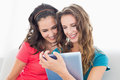 Two smiling young female friends using digital tablet in the living room at home Royalty Free Stock Photos