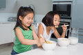 Two smiling young girls eating cereals in kitchen the at home Royalty Free Stock Photography