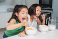 Two smiling young girls eating cereals in kitchen the at home Stock Images