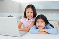 Two smiling young girls with laptop in kitchen portrait of the at home Royalty Free Stock Image