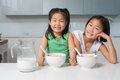 Two smiling young girls sitting with bowls in kitchen portrait of the at home Royalty Free Stock Images