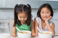 Two smiling young girls sitting with bowls in kitchen portrait of the at home Royalty Free Stock Photography