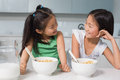 Two smiling young girls sitting with cereal bowls in kitchen the at home Stock Photography