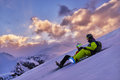 Two snowboarders on the slopes lie sideways a background of pink sunset clouds in mountains evening Royalty Free Stock Photography