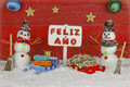 Two snowmen with a happy new year signpost with the words written on spanish holding sign Stock Photography