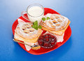 Two sour cherry cakes, milk and jam on plate Royalty Free Stock Images