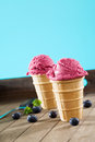 Two standing waffle cones with blueberry ice cream on wooden background Royalty Free Stock Photography