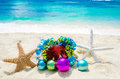 Two starfishes with christmas balls and gift on the beach holi box sandy in sunny day holiday concept Royalty Free Stock Photos