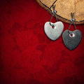Two stone hearts on red floral background hanging from a section of tree trunk velvet with roses flowers Stock Photography