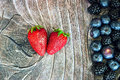 Two strawberries on wood background with other berries Stock Photo