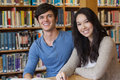 Two students in a library sitting at desk while learning and smiling Stock Images