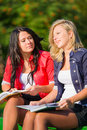 Two students read books on a bench Stock Photography