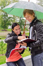 Two students under umbrella Stock Images