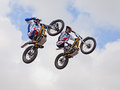 Two stunt biker make an acrobatic jump at the trial and motocross freestyle show during the motorcycle rally motosalsicciata on on Stock Photo