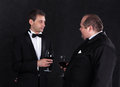 Two stylish businessman in tuxedos with glasses of red wine on black background Stock Photos