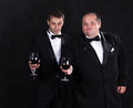 Two stylish businessman in tuxedos with glasses of red wine on black background Royalty Free Stock Photography