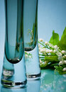Two stylish glass vases with flowers on blue Stock Photography