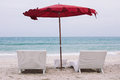 Two sun beds at the beach with red umbrella Royalty Free Stock Photo