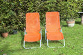 Two sun loungers in the garden orange side by side Royalty Free Stock Image