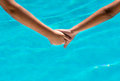 Two sun tanned young people holding hands Royalty Free Stock Photo