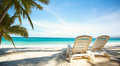 Two sunbeds on paradise beach with palms trees Royalty Free Stock Photography