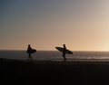 Two surfers walking towards the waves in the sunset on a late afternoon Stock Photo