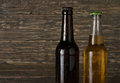 Two sweating, cold bottle of beer on dark wooden background Royalty Free Stock Photo