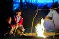 Two sweet boys, sitting around the campfire after sunset Royalty Free Stock Photo