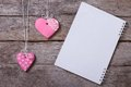 Two sweet pink heart cookies and a note on wooden board Stock Image