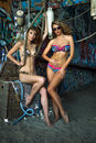 Two swimsuit models posing sexy in front of graffiti background with marine style accessories hanging on the wall made drift Stock Photo