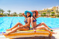 Two tanned girls at swimming pool relax of Royalty Free Stock Image