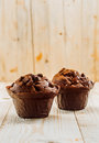 Two tasty chocolate chip muffins freshly baked in brown paper cups standing on a wooden table top in a rustic kitchen with a wood Stock Photos