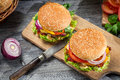 Two tasty homemade burgers old wooden table Royalty Free Stock Image
