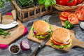 Two tasty homemade burgers and vegetables on old wooden table Stock Photography
